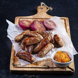Selbstgemachte Schweinswürste mit Geschmorte Zwiebeln mit Senf-Aprikosen-Chutney