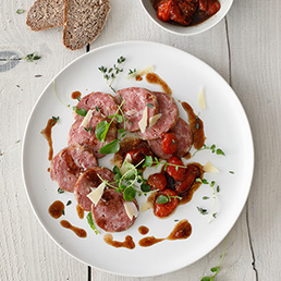 Warmes Carpaccio von Saucisson vaudois IGP mit Tomatenconfit und Berner Hobelkäse AOP